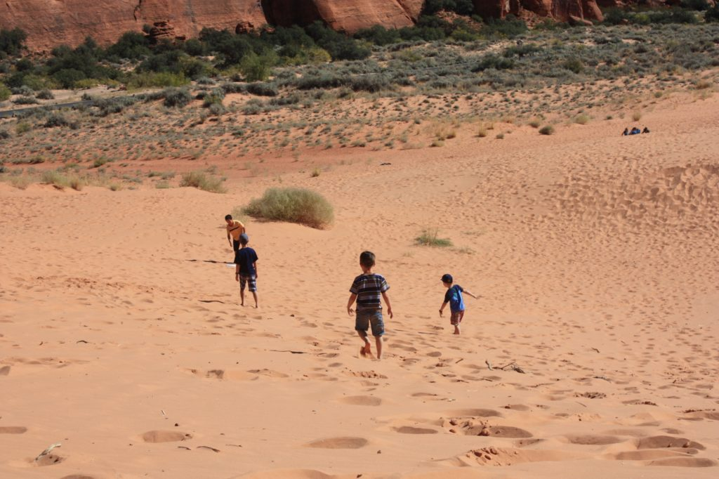 Boys running on the snow canyon sand dunes