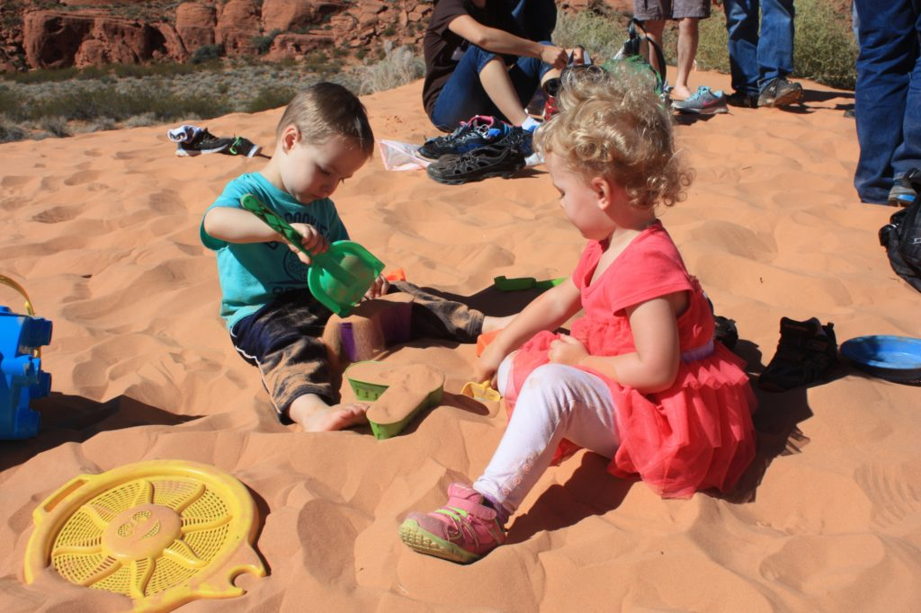 Kids playing in the snow canyon sand dunes.
