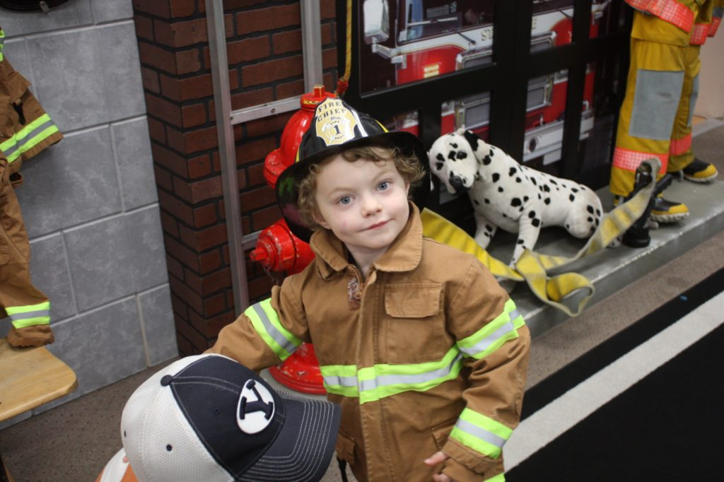 A boy putting on a fire fighter suit