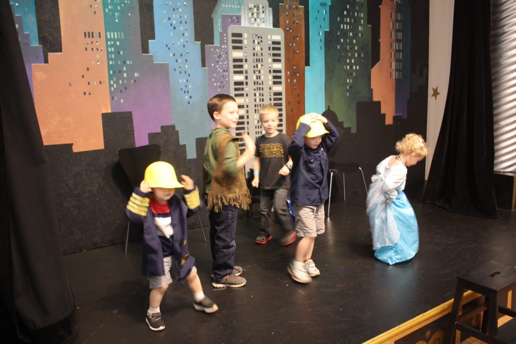 children on a stage at the museum