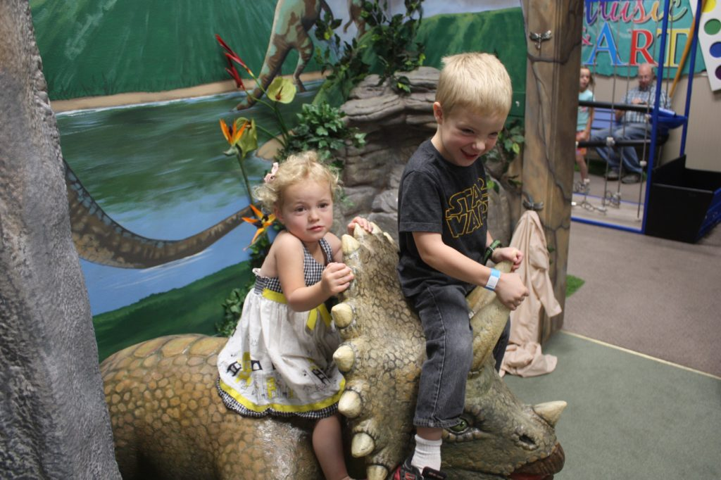 a boy and a girl on a dinosaur at the museum