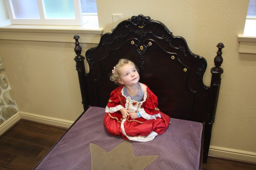 A little girl on the princess bed in the museum