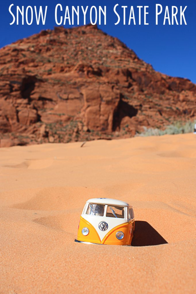 Yellow van in the sand at Snow Canyon with red rock mountain